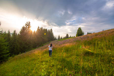 Girl enjoy pure nature. Walk over the field to meet sunset.