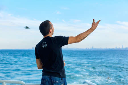 The guy throws bread to the seagulls flying over the ferry. Istanbul, Turkey - 07/28/2017