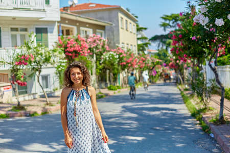 A charming brunette girl walks along the street of Buyukada island in Turkey. Summer sunny day and blossoming trees.