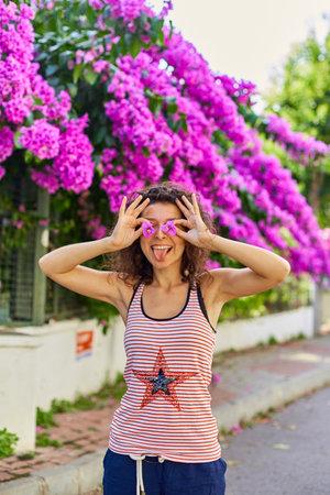 Beautiful young girl model brunette posing with blooming purple flowers in Turkey on the island of Buyukada.