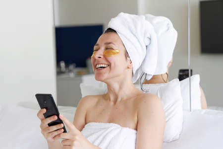 After a shower, the girl is wrapped in a towel and wears cosmetic patches for the skin under the eyes. Looks at the cell phone. Cosmetic procedures at home. Getting ready for a date.