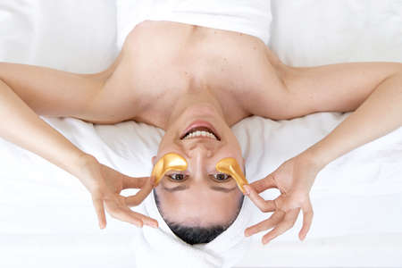 After a shower, the girl is wrapped in a towel and wears cosmetic patches for the skin under the eyes. Cosmetic procedures at home. Standard-Bild