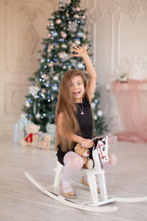 Beautiful little girl rejoices at the wooden rocking horse, a Christmas present from Santa. Standard-Bild