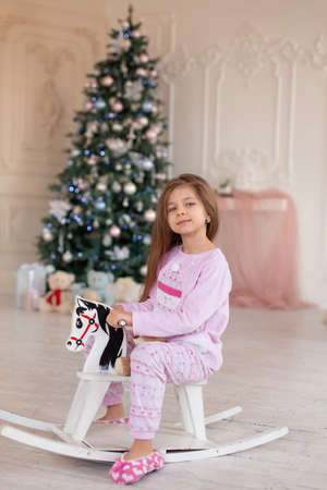 A beautiful little girl in pink pajamas rejoices in a wooden rocking horse, a gift from Santa for Christmas. Standard-Bild