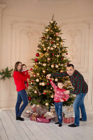 Happy family decorate the Christmas tree indoors together. Loving family. Merry Christmas and Happy Holidays. Standard-Bild