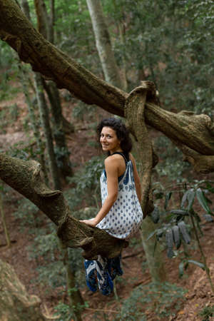 The girl sits on a huge liana tree branch in the jungle. Standard-Bild