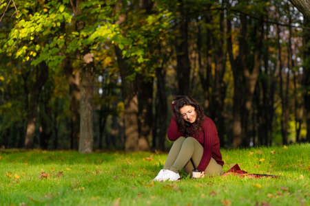 Pretty girl enjoys autumn and the beauty of nature sitting on a green lawn in the park. Autumn mood.