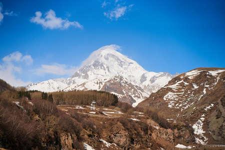 Automobile mountain road to the bottom of Mount Kazbegi. Snow cap on the top of the mountain.