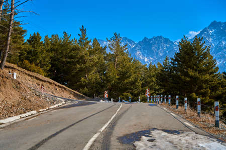 Dangerous winding road among the mountains. Mountain streamer in early spring. Spectacular mountain landscape.
