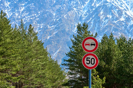 Road sign of speed limit and prohibiting overtaking on a serpentine mountain road. Dangerous high-mountain roads. Banque d'images