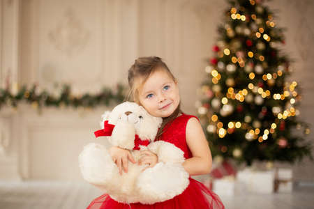 A little girl is enjoying her new teddy bear given by Santa Claus for Christmas. Banque d'images