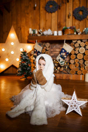 A little girl in warm clothes meets Christmas night in a wooden hut. Banque d'images