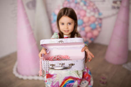 Little girl fashionista chooses stylish outfit and accessories for her look.