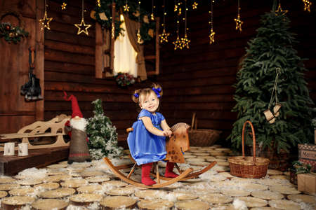 A little girl enjoys riding a rocking horse that was given to her for Christmas.