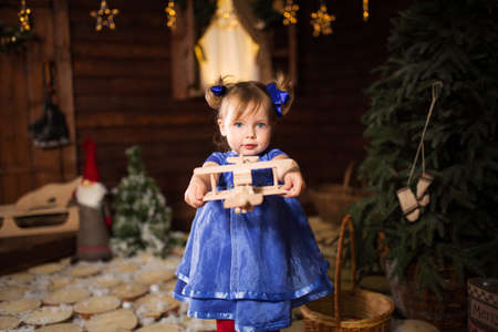 A child plays with a wooden plane that Santa gave him for Christmas. Banque d'images