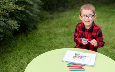 A little boy drawing a picture in the garden (outdoors). Wearing glasses and an eye patch (plaster, occluder) to prevent amblyopia and strabismus (squint, lazy eye). Child vision disease problem. Standard-Bild