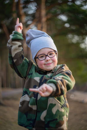 a little funny active kid in glasses wearing a hat and a jacket in camouflage colors enjoying nature smiling and waving hands while walking in park at blurred background