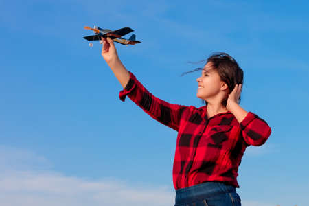A young woman in a red checked shirt and disheveled hairs against the blue sky launches a toy paper airplane. Image on the theme: tourism and travel, aviation, freedom and inspiration. Banque d'images