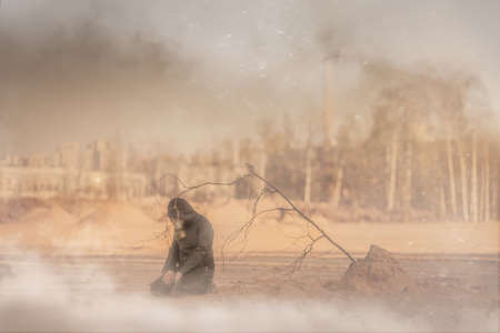 A man in a gas mask is kneeling in a desolate urban post-apocalyptic landscape. A dead tree sapling is nearby. There is dust, smoke, smog and ash in the air. Despair. Global environmental threat.