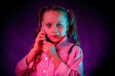 The little girl is talking on the phone. A surprised, startled face. Studio, neon light, gel filters, turquoise, magenta, purple.