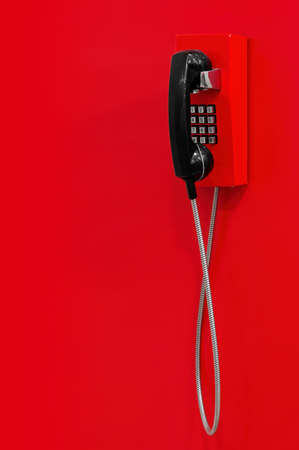 Red wall telephone (taxophone) on red background. Emergency call to 112, 911, fire and rescue, medic, police, urgent message.