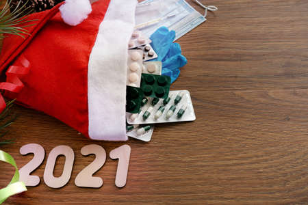 Santa Claus hat with medical supplies. New years composition. The view from the top. Numbers 2021. High quality photo Stock Photo
