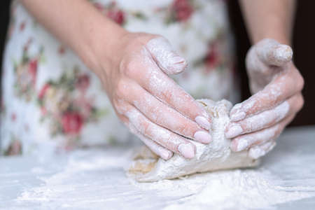 A young girl kneads dough with her hands on the table. High quality photo