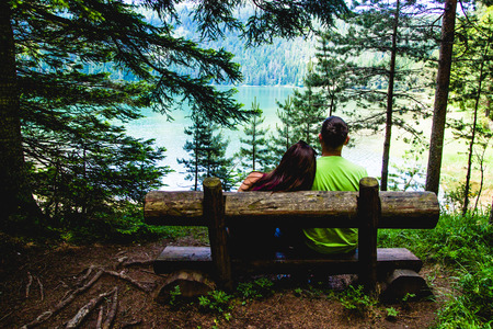 Lovely Couple in a Park on a Wooden Pew, Montenegro, Durmitor Park Stock Photo