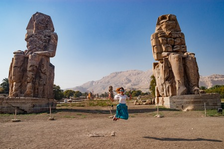 Junping near the ruins of statues in Luxor, Egypt Stock Photo