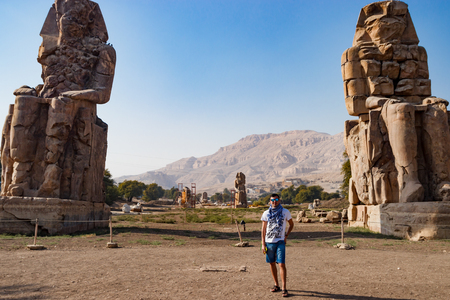 Man near the ruins of statues in Luxor, Egypt