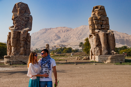 Couple near the ruins of statues in Luxor, Egypt