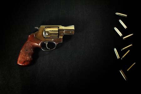 Revolver gun and Bullet 38 mm size on black fabric background.