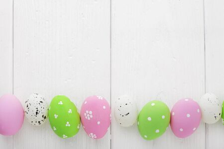 colorful easter eggs on white wooden background, copy space