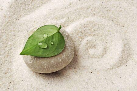 zen meditation stone. Round rock in sand texture background. Concept for yoga or spa welness treatment Standard-Bild