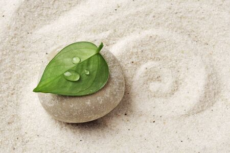 zen meditation stone. Round rock in sand texture background. Concept for yoga or spa welness treatment Stock Photo