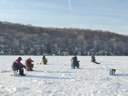 ice chest: voronezh; russia: fishermen sitting on their fishing chests on river ice Stock Photo