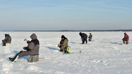 ice chest: winter fishermen sitting on their fishing chests on river ice