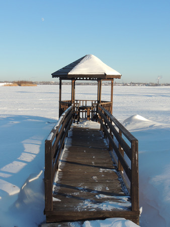 footway: Wooden gazebo and planked footway by the covered by ice pond on a clear sunny winter day in a sanatorium on the outskirts of the city.  Stock Photo