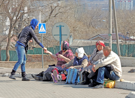 kerb: Orthodox Easter. Young Women in a headscarf gives charity into the hands of the beggars sitting side by side on the road kerb in the square at the Pokrovsky Cathedral. The Group of beggars consists of three senior women adult and one mature adult man. On