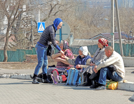 beggars: Orthodox Easter. Young Women in a headscarf gives charity into the hands of the beggars sitting side by side on the road kerb in the square at the Pokrovsky Cathedral. The Group of beggars consists of three senior women adult and one mature adult man. On