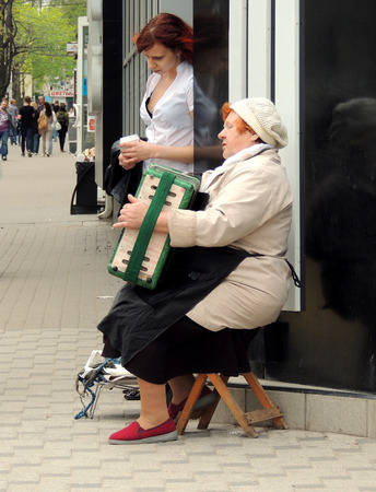 attentively: Street mature women musician in the knitted beanie sitting on the wooden camp stool in the city street and playing the accordion. Young women with cup in the hands attentively listens to her standing against the wall Editorial