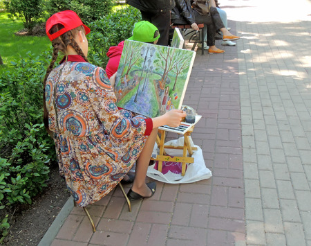 late teens: Sitting on camp stool the late teens girl painter have a good look at the holding painted landscape. It is open outdoors lesson of art school in the city park on the Victory Day celebration.