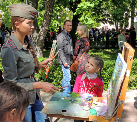 elementary age girl: Young women in a field cap with brushes in the hands drawing on the canvas in the easel on the city square during the Victory Day celebration. Elementary age girl with the plaits and cravat attentively watches her work. Editorial
