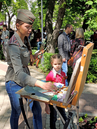 elementary age girl: Young women in a forage cap with plait drawing on the canvas in the easel on the city square during the Victory Day celebration. Elementary age girl with the neckerchief attentively watches her work.