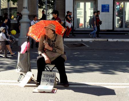 ladys: Spectacled senior adult woman with lady39s hat and opera glasses in the hand under the umbrella on the city street at sunny redletter day offering city dwellers to be weighed on a springbalance
