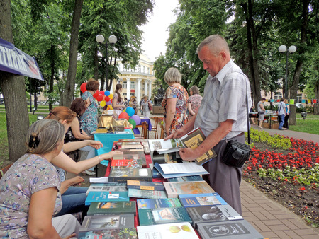 mature men: Mature men chooses books on the stall to buy them on the book fair in the public garden