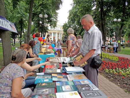 uomini maturi: Uomini maturi sceglie libri sulla bancarella di comprarli sulla fiera del libro in giardino pubblico