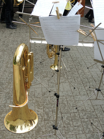 notation: Tuba and music stand with musical notation on the sidewalk in the rain