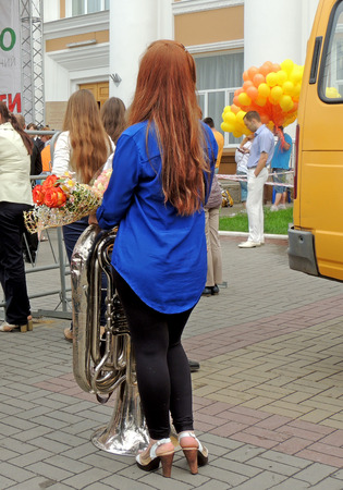tuba: Young redhaired women with tuba and bouquet of roses stand on sidewalk among spectators