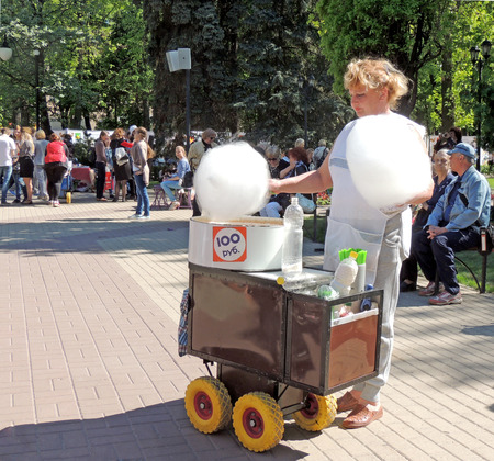 hand cart: Saleswoman of cotton candy with hand cart in the city public garden